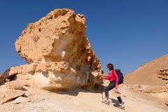 女性远足者在岩石登高 免版税库存图片