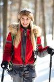女性远足者在森林里在冬天 库存照片
