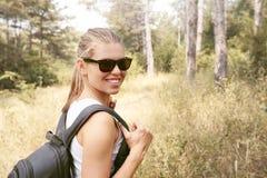 女性远足者在森林里 免版税库存照片