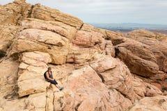 女性远足者坐一座山在沙漠 图库摄影