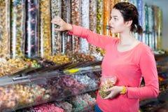 年轻女性选择糖果 图库摄影