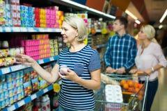 女性选择水果酸牛奶 免版税图库摄影