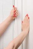 女性递whith修指甲和盲人在窗口 图库摄影