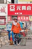 女性道路清扫工在商店地区,北京,中国 免版税库存照片