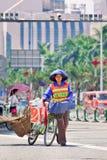 女性道路清扫工witj自行车,珠海,中国 库存图片