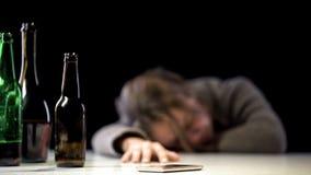 女性遭受的醇类中毒睡觉在桌上的电话附近的,卫生保健 免版税库存照片