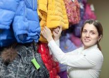 女性采购员选择冬天夹克 免版税图库摄影