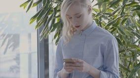 女性金发碧眼的女人得到在电话的sms并且在绿色植物附近微笑 股票录像