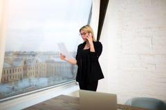 女性金融家藏品简历和叫与手机 库存照片