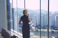 女性银行家在与都市风景视图和拷贝空间的办公室内部近的窗口里站立 库存图片