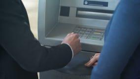 女性银行雇员显示新的客户如何与ATM,好服务一起使用 股票视频