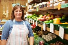 女性销售辅助在农厂商店菜柜台  免版税库存照片