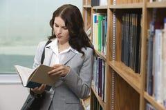 女性阅读书在图书馆里 免版税图库摄影
