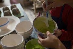 女性陶瓷工和男孩绘画的中间部分滚保龄球 免版税库存图片