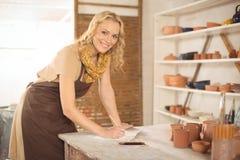 女性陶瓷工文字画象在笔记本的 免版税库存图片