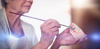 女性陶瓷工绘画特写镜头在碗的 库存图片