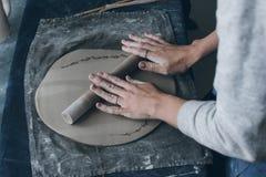 女性陶瓷工辗压黏土的手 免版税库存图片