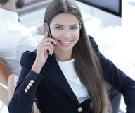 女性雇员谈话在与客户的机动性 库存图片