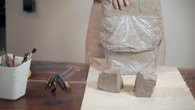 女性雕刻家在表上把灰色黏土三个片断,特写镜头视图放 影视素材