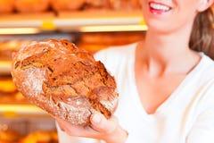 女性面包师在她的面包店 免版税库存图片