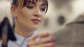女性面孔接近的射击在衣裳附近机架的在衣物商店 股票视频