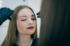 女性面孔特写镜头在眼眉更正做法期间的 免版税图库摄影