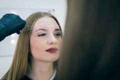 女性面孔特写镜头在眼眉更正做法期间的 库存照片