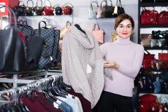 年轻女性顾客决定温暖的毛线衣 库存图片