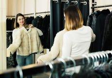 女性顾客审查的白色貂皮夹克 免版税图库摄影