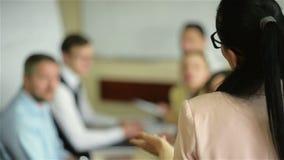 女性领导人经理教练谈话与雇员小组被会集在介绍报告新的经营计划的合作会议上 股票录像