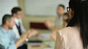 女性领导人经理教练谈话与雇员小组被会集在介绍报告新的经营计划的合作会议上 股票视频