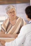 女性领退休金者在医生办公室 库存照片