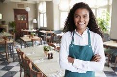 女性餐馆经理画象在空的餐厅 免版税库存照片