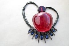 女性香水说谎在黑串的红色美丽的玻璃透明瓶以用被扯拽的bl装饰的心脏的形式 免版税图库摄影
