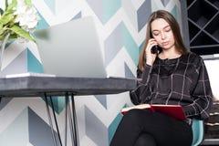 女性骄傲的新闻工作者谈话在手机和我们网书 免版税库存照片