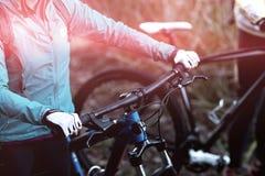 女性骑自行车的人的中央部位有登山车的 库存照片