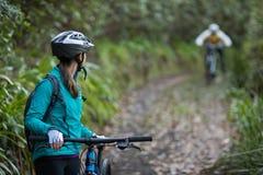 女性骑自行车的人等待的男性骑自行车的人 免版税库存照片