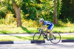 女性骑自行车者在路骑一辆赛跑的自行车 免版税库存图片