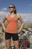 女性骑自行车者用在腰部的手在山 图库摄影