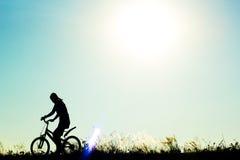 女性骑自行车者骑马运动的剪影在背景的 免版税图库摄影