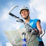 女性骑自行车者,读地图 免版税库存图片