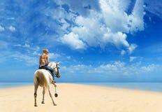 年轻女性骑马她的马在海 库存图片