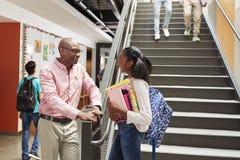 女性高中学生谈话与繁忙的走廊的老师 免版税库存图片