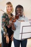 女性高中老师画象有演奏Viol的学生的 库存图片