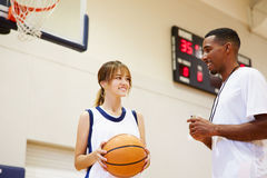 女性高中蓝球运动员谈话与教练 库存照片