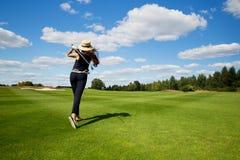年轻女性高尔夫球运动员,后面看法画象  库存图片