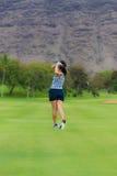 女性高尔夫球运动员击中高尔夫球 免版税库存图片