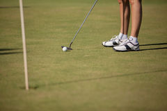 女性高尔夫球运动员以绿色 免版税库存图片