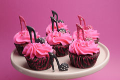 女性高跟鞋短剑穿上鞋子装饰的桃红色和黑红色天鹅绒杯形蛋糕 免版税库存照片