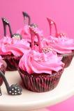 女性高跟鞋短剑鞋子装饰了桃红色和黑色红色天鹅绒杯形蛋糕-接近在桃红色杯形蛋糕。 库存图片